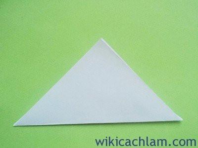 Bước 1: Bạn hãy cắt giấy thành hình vuông rồi gấp chéo góc thành hình tam giác. Độ to nhỏ tùy thuộc vào việc bạn muốn bông hoa của bạn to hay nhỏ mà cắt cho phù hợp nhé.
