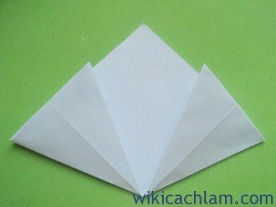 Bước 4: Tiếp đó, bạn gấp góc nhọn vào trong như hình. Tiếp theo, bạn gấp đôi phần cánh hoa hai bên lại, dùng tay niết mạnh xuống  để giữ nếp gấp