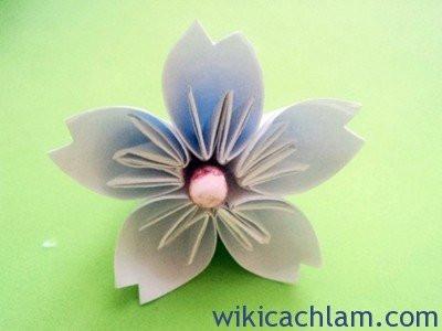 Sau đó bạn tiếp tục gắn các cánh lại với nhau thành bằng băng dính 2 mặt tại các điểm tiếp xúc giữa các cánh với nhau. Nhằm để cánh hoa đào mướt hơn và trông thật hơn bạn hãy dùng kéo cắt khoét đầu nhọn của cánh đào. Để làm nhụy hoa thì bạn có thể dùng xốp tròn nhuộm màu nhụy vàng hoặc hồng rồi dùng dây thép xiên vào xốp và luồn vào giữa của bông hoa, Vậy là bạn có được bông hoa đào như hình rồi đó