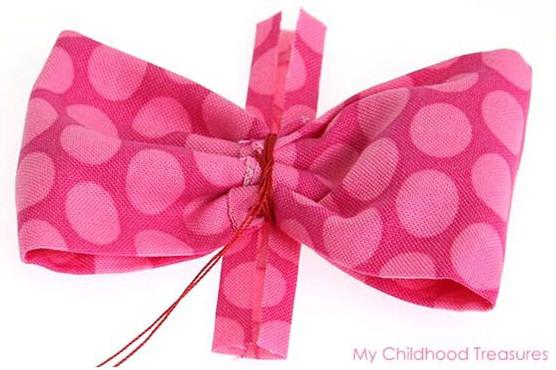 Dùng một miếng vải nhỏ và keo cố định phần chỉ buộc lại để che đi phần chỉ buộc và làm nơ đẹp hơn